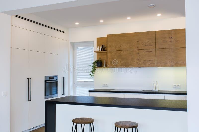 Conception moderne de cuisine dans l'intérieur léger avec les accents en bois image stock
