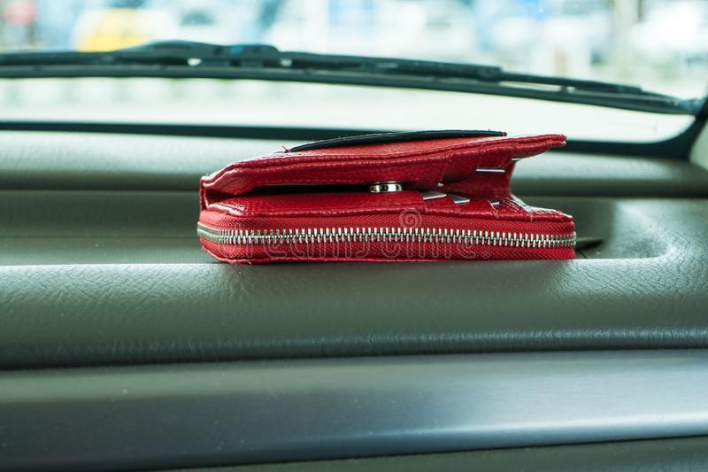 Red purse on dashboard in car. Conception photo of red purse with zipper lying on the dashboard of a car, symbol for money, temptation, theft, carelessness stock images