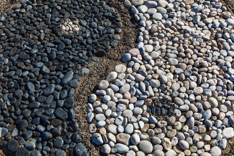 Yin and yang of stones. The conception of yin and yang is laid with stones on the sand,Yin and yang of stones royalty free stock image