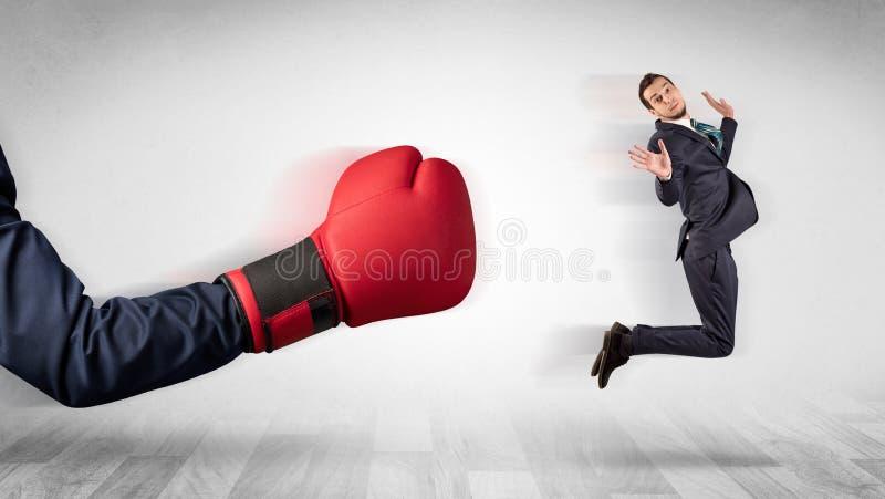 Красная кладя в коробку перчатка стучает вне меньшим бизнесменом стоковое фото rf