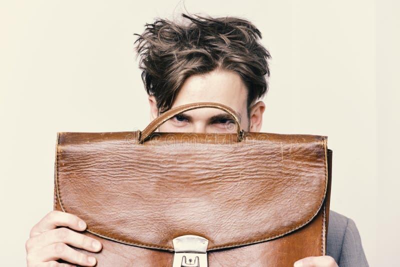 Concepto académico del estilo y del negocio Empollón con el pelo sucio y la mirada confiada Hombre que oculta detrás de la carter imagen de archivo libre de regalías