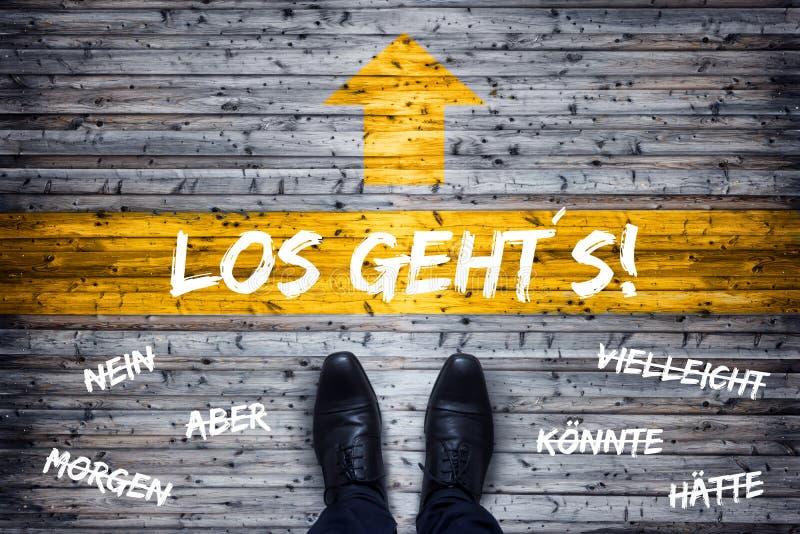 Concepto alemán del negocio - traducción: ¡Aquí vamos! - Zapatos negros en la línea de salida foto de archivo libre de regalías