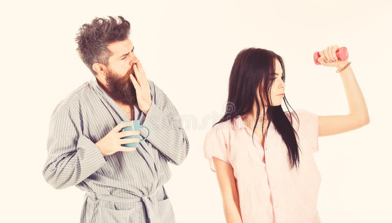 Concepto alternativo de la forma de vida Muchacha con pesa de gimnasia, hombre con la taza de caf? Pares en amor en el pijama, so foto de archivo