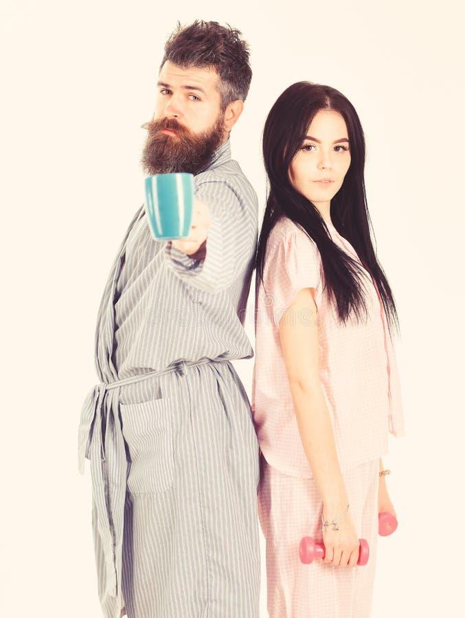 Concepto alternativo de la forma de vida Muchacha con pesa de gimnasia, hombre con la taza de caf? Pares en amor en el pijama, so imágenes de archivo libres de regalías