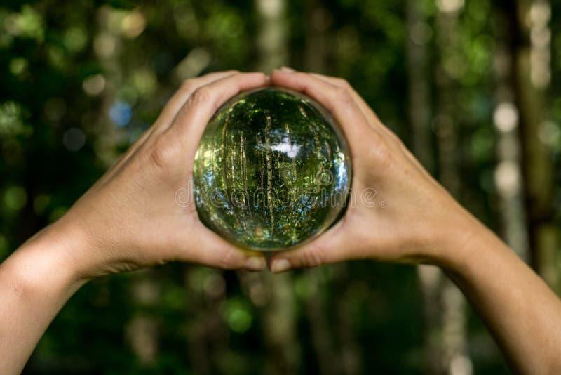 Concepto ambiental del mundo Globo cristalino en mano humana en bokeh verde y azul hermoso fotografía de archivo