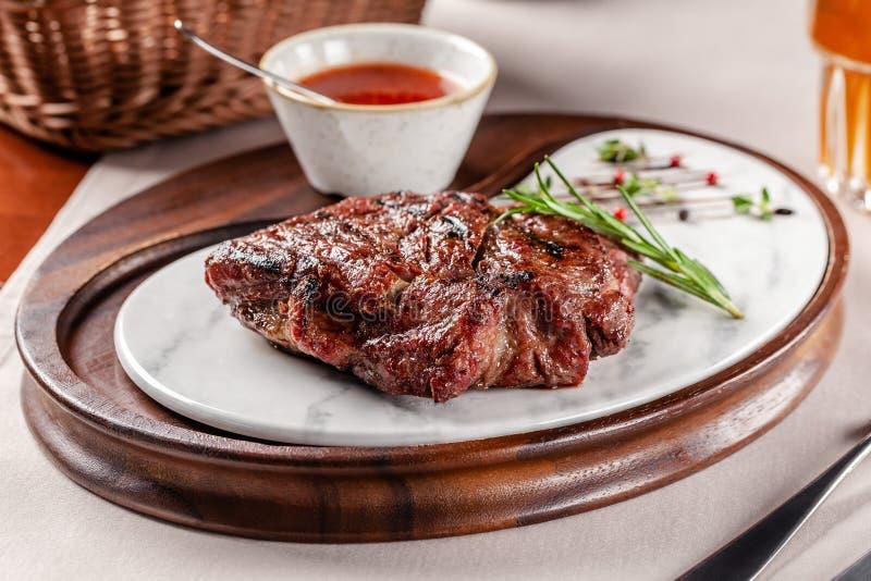 Concepto americano de la cocina Filete del cerdo con la salsa de barbacoa roja del tomate Platos de porción en un tablero de made imagenes de archivo