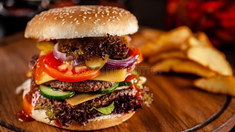 Concepto americano de la cocina Una hamburguesa hecha en casa grande con una empanada doble de la carne del cerdo y de la ternera foto de archivo libre de regalías