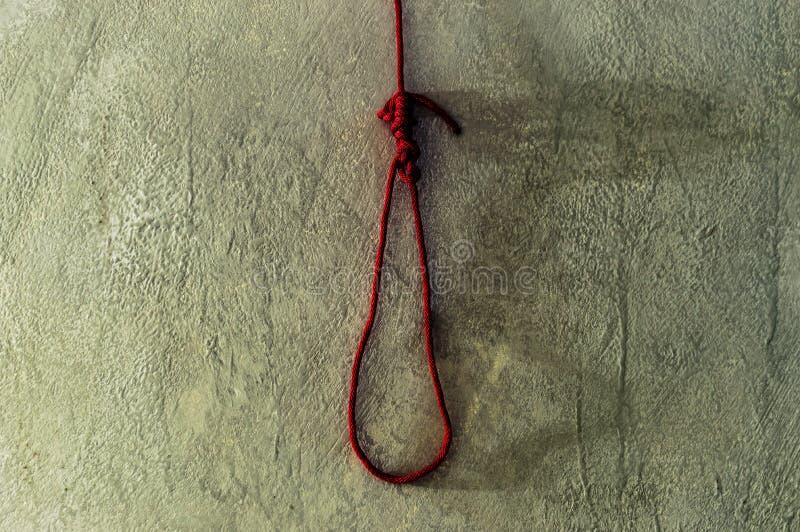 Concepto asustadizo y de la muerte con la soga de la cuerda roja para la muerte en el cemento fotos de archivo