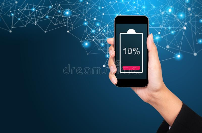 Concepto bajo de la batería Punto bajo de la batería en la pantalla del smartphone en mano de la empresaria imagen de archivo