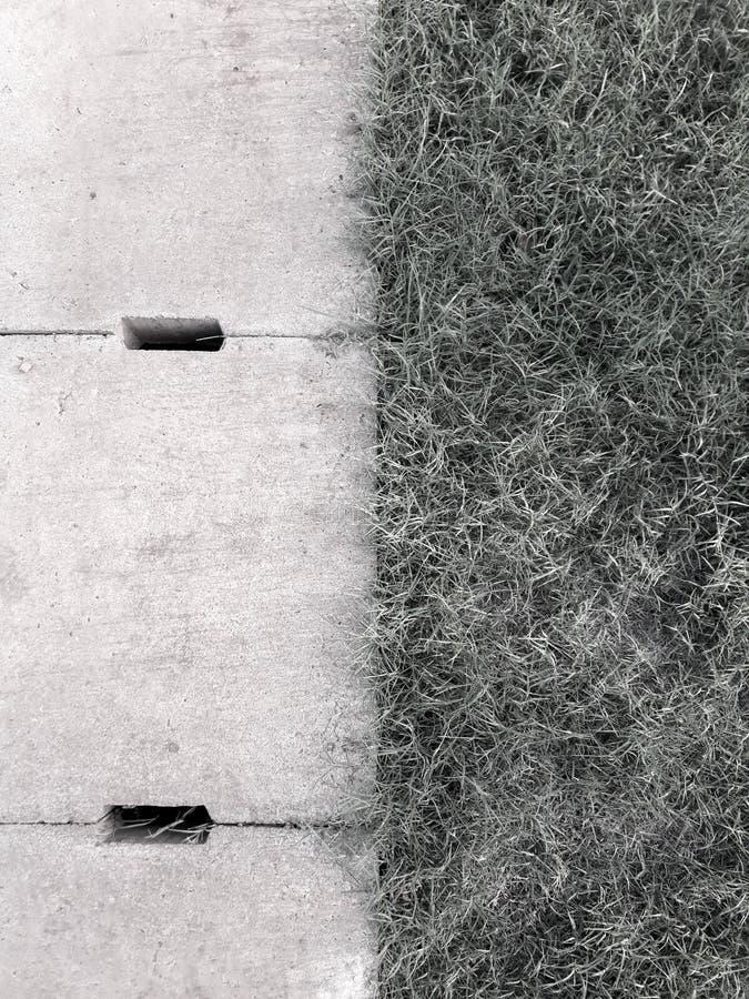 Concepto blanco y negro rejilla del dren del cemento e hierba verde con el fondo abstracto fotografía de archivo libre de regalías