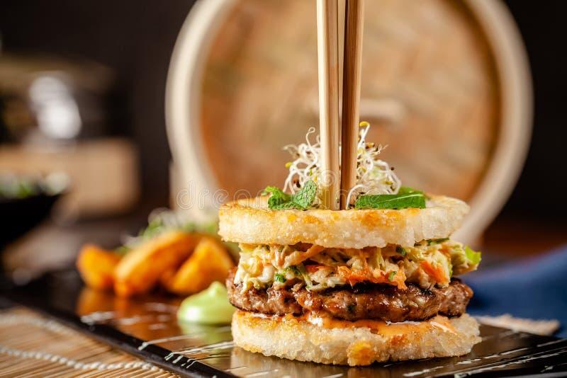 Concepto Cacerola-asiático de la cocina Hamburguesa japonesa del sushi hecha del pan del arroz, empanadas de la carne del pollo y fotos de archivo