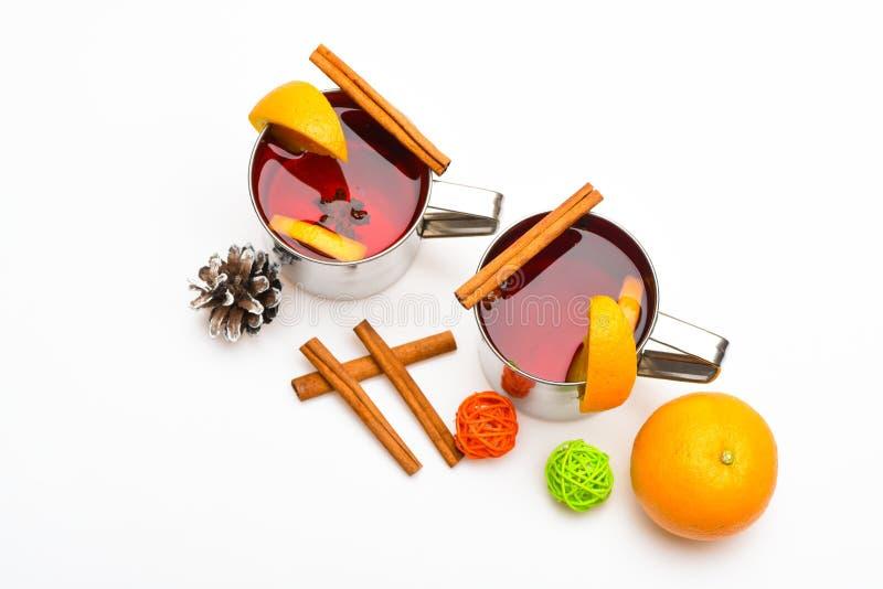 Concepto caliente de las bebidas del invierno Tazas con el vino reflexionado sobre o la bebida caliente cerca de la fruta anaranj imagen de archivo libre de regalías