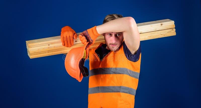Concepto cansado del trabajador Hombre en el barrido del casco y de los guantes protectores sudado de la frente, fondo azul carpi imagen de archivo libre de regalías