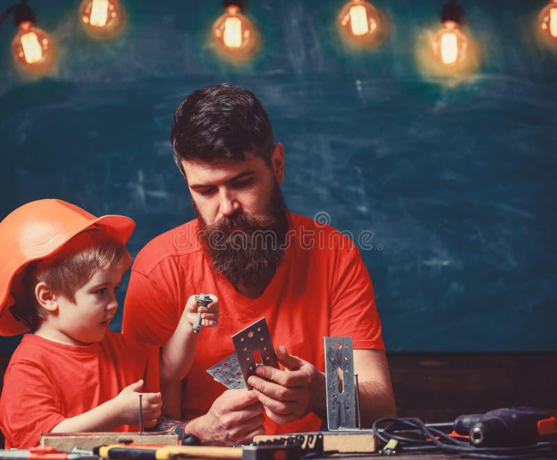 Concepto casero de la educaci?n El muchacho, ni?o en casco protector hace a mano, reparando, hace artes con el pap? Padre con imágenes de archivo libres de regalías
