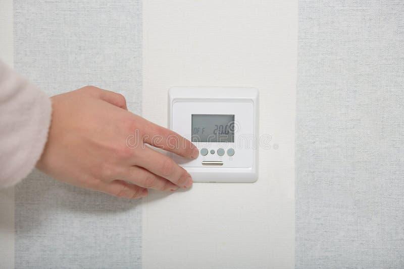Concepto casero elegante El interruptor del botón de los puches de las manos en la pared blanca, regula temperatura en plano o si imagen de archivo libre de regalías