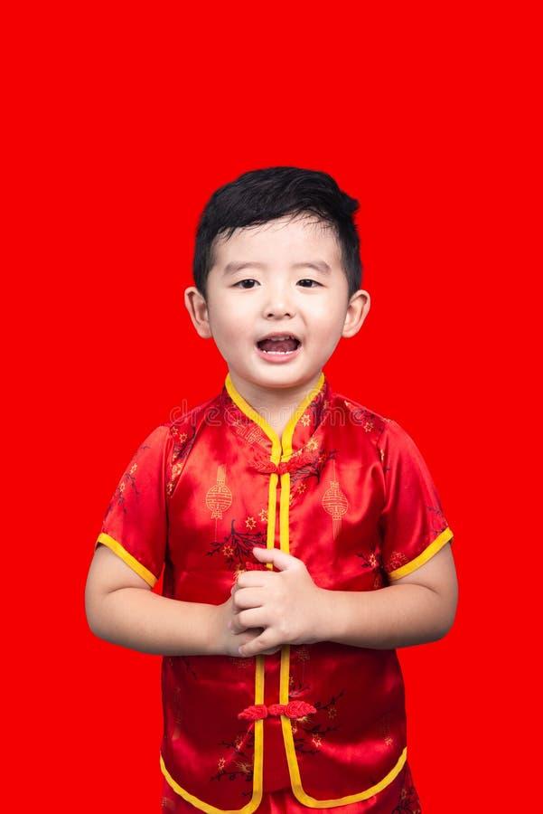 Concepto chino del A?o Nuevo, muchacho asi?tico lindo en el traje chino tradicional rojo aislado en rojo con la trayectoria de re imagen de archivo