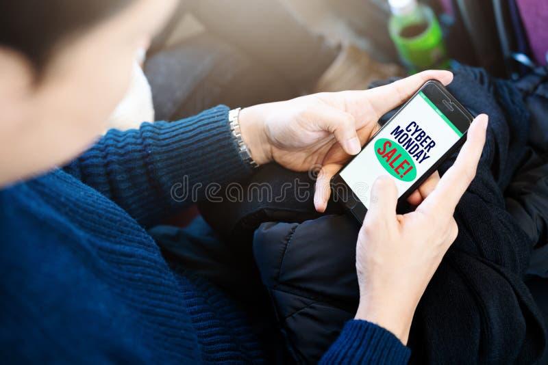 Concepto cibernético del descuento de la liquidación de la venta de lunes, hombre que hace compras en línea por smartphone imagen de archivo