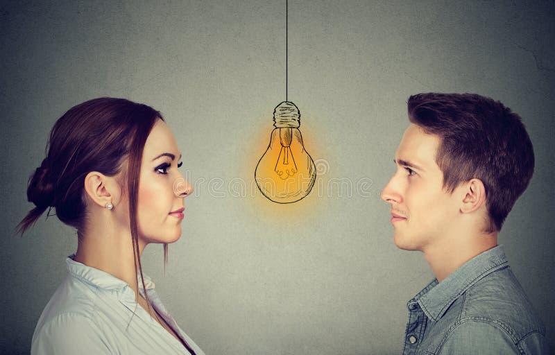 Concepto cognoscitivo de la capacidad de las habilidades, varón contra hembra Hombre y mujer que miran la bombilla brillante imagen de archivo
