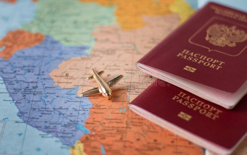Concepto con los documentos de viaje del pasaporte, aeroplano del viaje y del turismo en fondo del mapa del mundo imagen de archivo