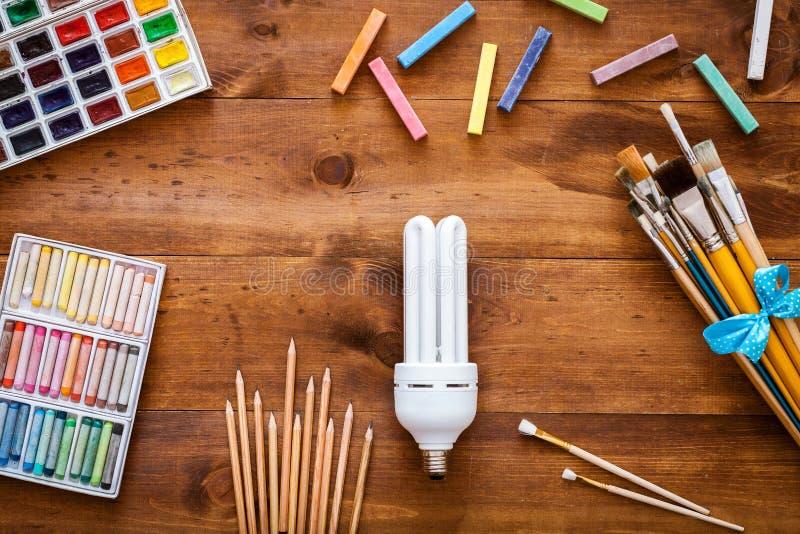 Concepto creativo de la imaginación de la fantasía de la idea del arte, bombilla, brochas, caja de pinturas con las acuarelas, cr imágenes de archivo libres de regalías