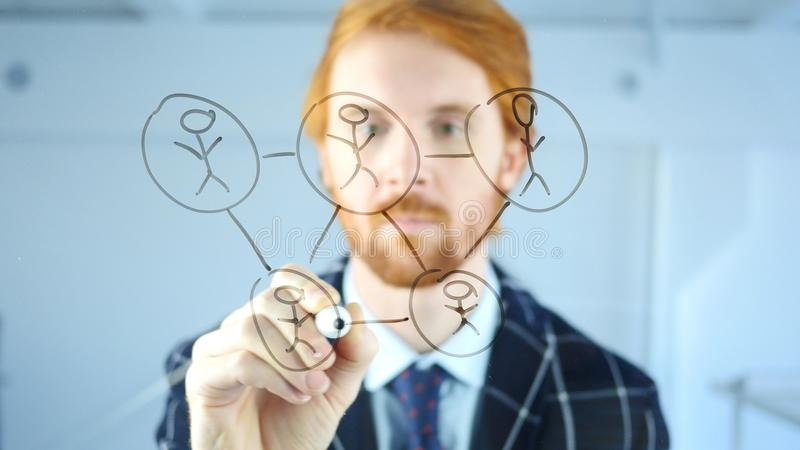 Concepto creativo de la red de la gente del dibujo del hombre sobre el vidrio transparente en la oficina, pelos rojos fotografía de archivo libre de regalías