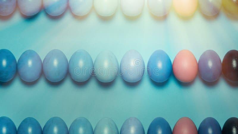 Concepto creativo de Pascua Huevos de Pascua coloreados de una pendiente azul en fila en un fondo azul Visi?n desde arriba fotos de archivo libres de regalías