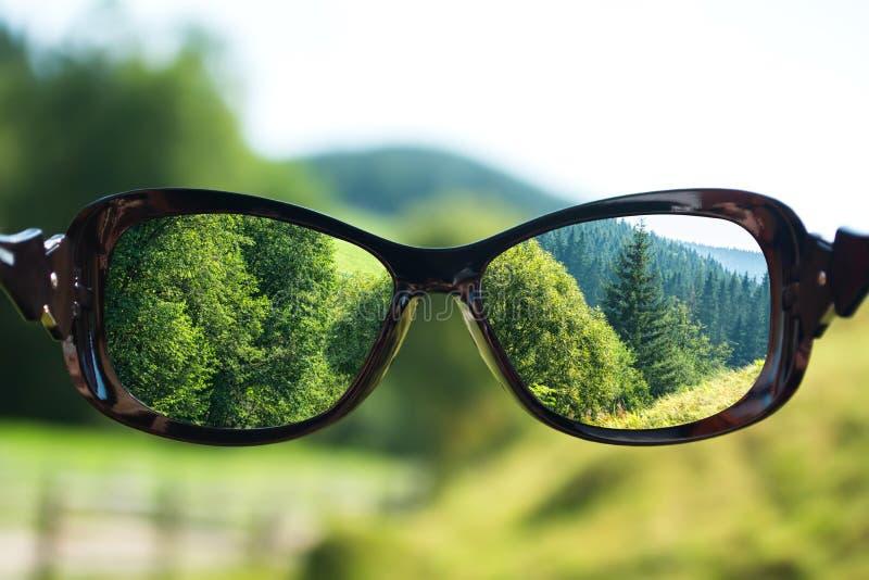Concepto creativo sobre la visión pobre Paisaje enfocado en lentes de los vidrios fotografía de archivo libre de regalías