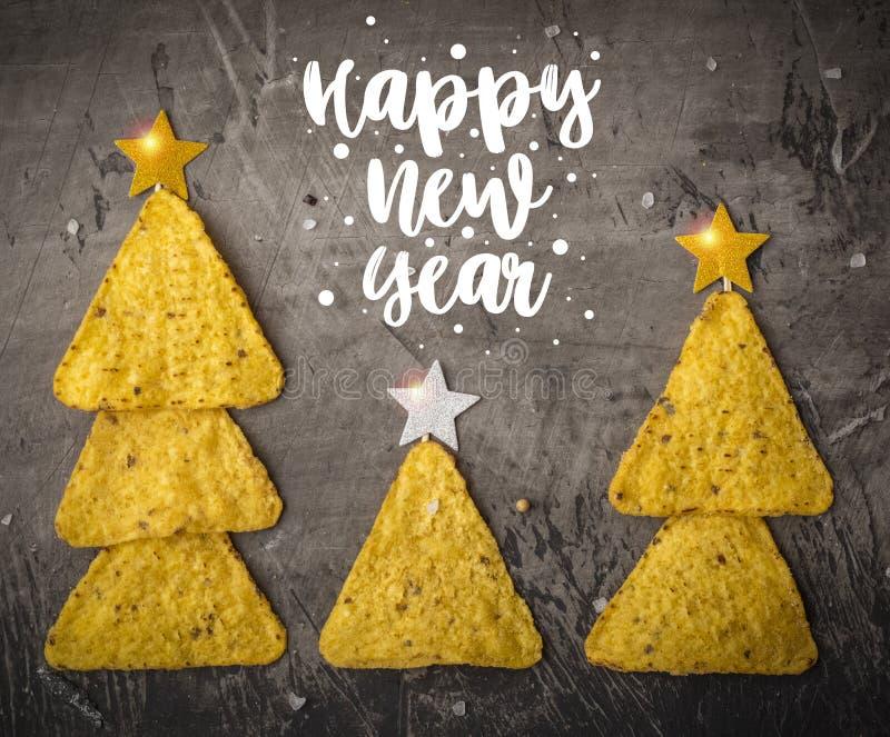 Concepto de Año Nuevo de los nachos mexicanos Árboles de navidad hechos de los nachos de los microprocesadores con queso en un fo imagen de archivo libre de regalías