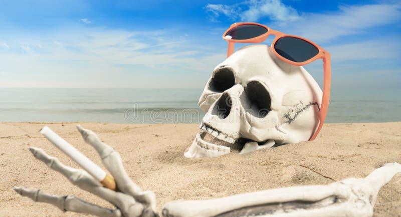 Concepto de adicción al cigarrillo un esqueleto con un cigarrillo yace en la playa imagen de archivo libre de regalías