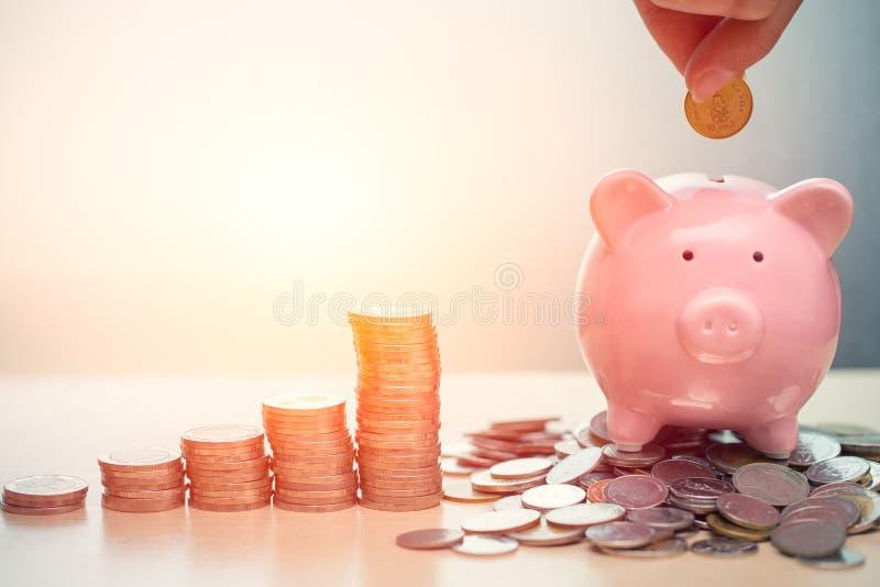 Concepto de ahorro del dinero de la mano, hucha con la moneda fotos de archivo