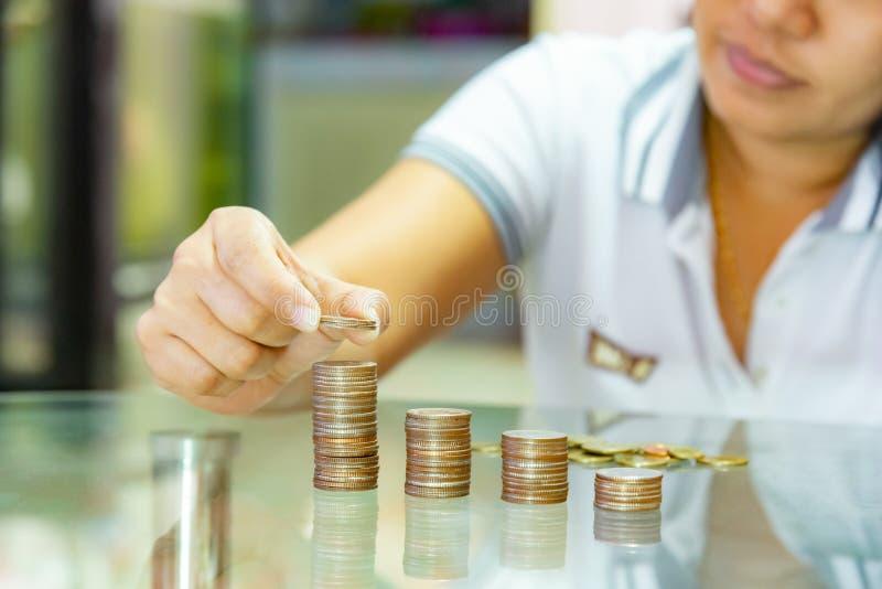 Concepto de ahorro del dinero, mujer que apila monedas en columnas de pila cada vez mayores fotografía de archivo