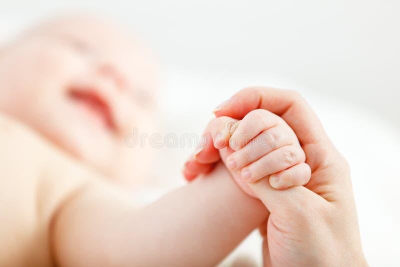Concepto de amor parental mano del bebé que sostiene el finger de la madre foto de archivo libre de regalías