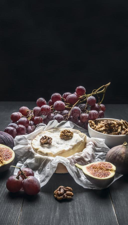 Concepto de aperitivos para el vino, el queso del camembert, las uvas oscuras, las nueces y los higos con la miel, en el espacio  fotografía de archivo