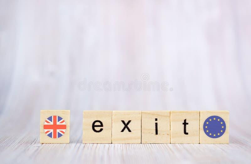 Concepto de Brexit Palabra de la salida escrita en los bloques de madera con británicos y las banderas de la UE Texto de la salid foto de archivo libre de regalías
