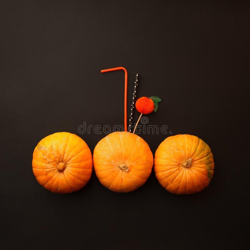 Concepto de cócteles anaranjados de la calabaza de Halloween en fondo del negro del misterio Bebida festiva, tendencia mínima foto de archivo