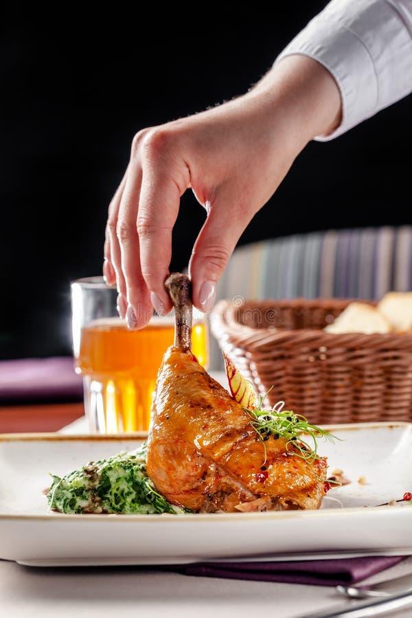 Concepto de cena en restaurante japonés Guarnición de la espinaca con crema y piernas de pollo esmaltadas en salsa picante Vino d fotos de archivo