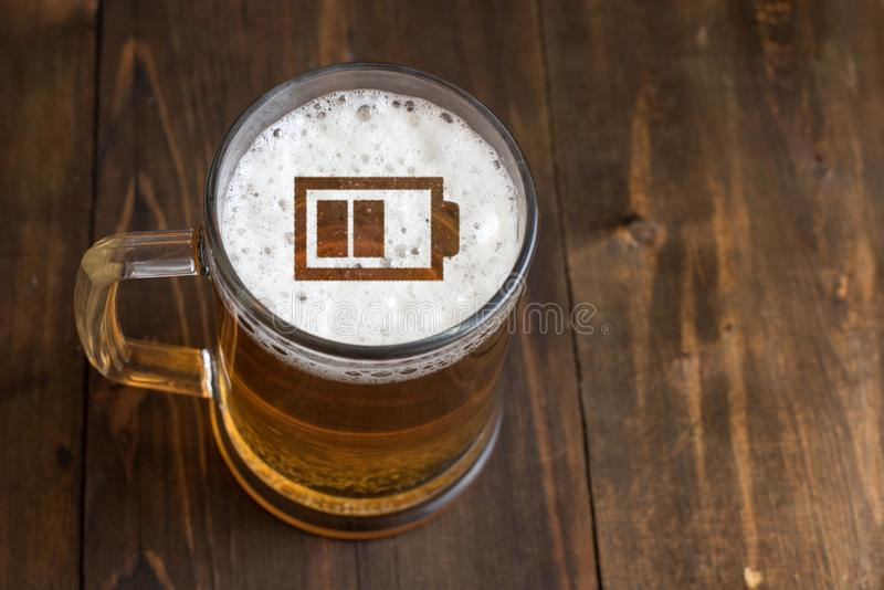 Concepto de cerveza de la energía Firme la pequeña batería en la espuma de la cerveza en vidrio fotos de archivo