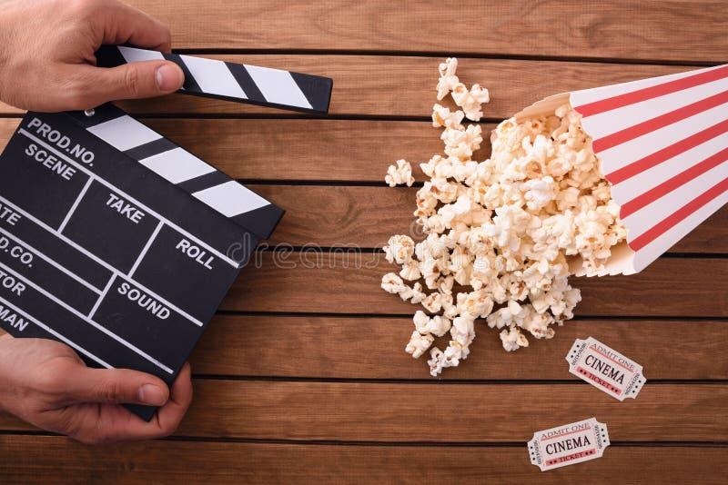 Concepto de cine de observación con la mano con clapperboard y popco fotografía de archivo libre de regalías