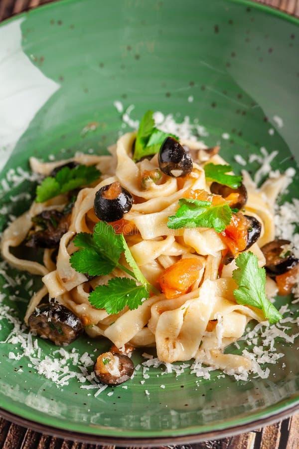 Concepto de cocina italiana Tallarines con las verduras, los tomates, las aceitunas y el queso parmesano Adornado con perejil por imágenes de archivo libres de regalías
