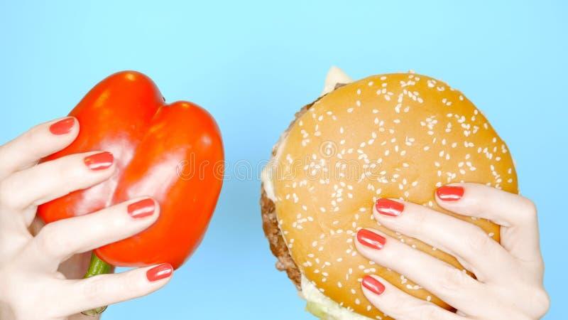 Concepto de comida sana y malsana pimienta roja dulce contra las hamburguesas en un fondo azul brillante Manos femeninas foto de archivo libre de regalías