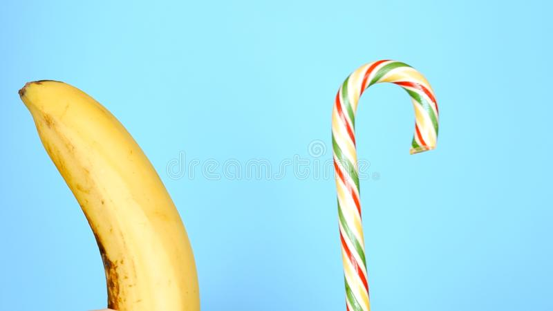 Concepto de comida sana y malsana pl?tano contra el caramelo en un fondo azul brillante imagen de archivo