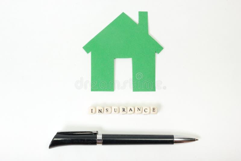 Concepto de compra y de seguro de la vivienda Tabla con la opinión superior de las fuentes - pluma, casa modelo verde del escrito fotos de archivo