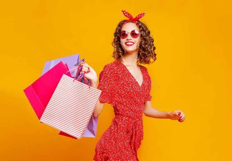 Concepto de compras de las compras y ventas de la chica joven feliz con los paquetes en fondo amarillo fotografía de archivo