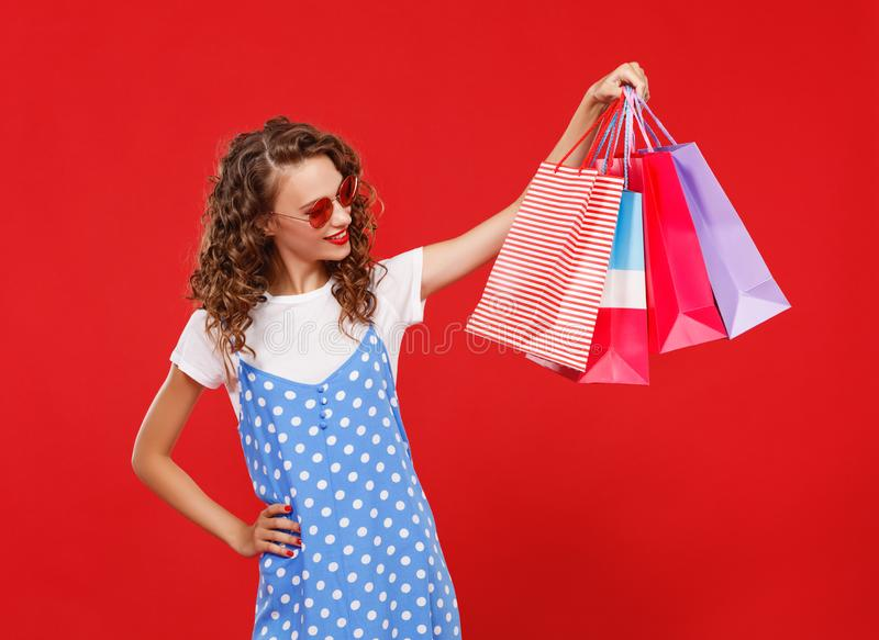 Concepto de compras de las compras y ventas de la muchacha feliz con los paquetes en fondo rojo foto de archivo
