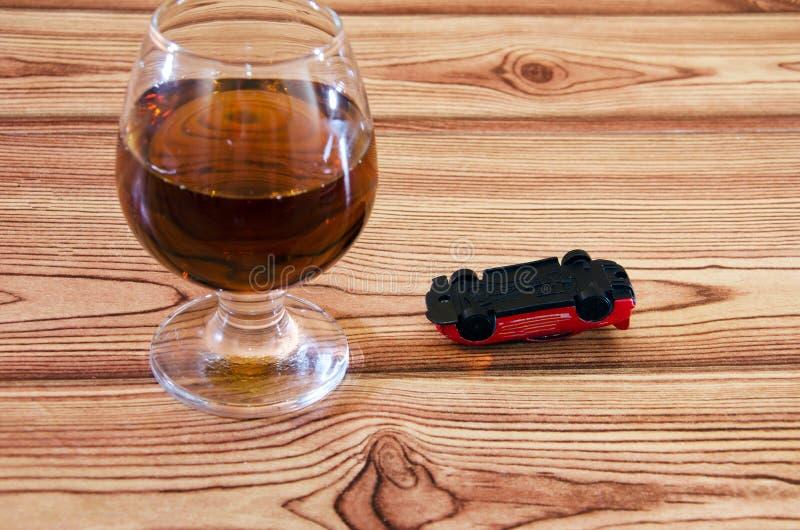 Concepto de conducción sobrio Copa de vino y vuelto hacia arriba, coche del juguete imagen de archivo libre de regalías