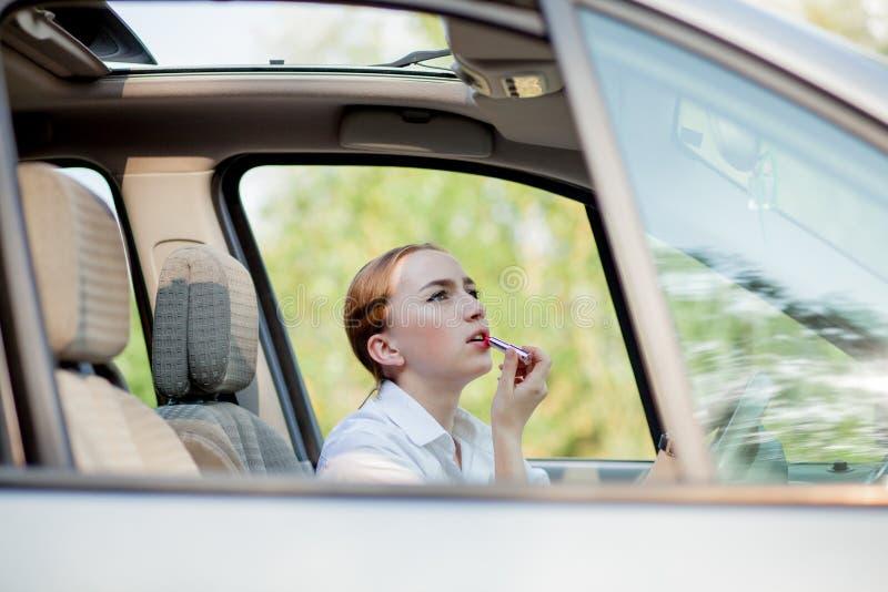 Concepto de conducci?n del peligro El adolescente pelirrojo del conductor de la mujer joven que pinta sus labios que hacen la apl imágenes de archivo libres de regalías