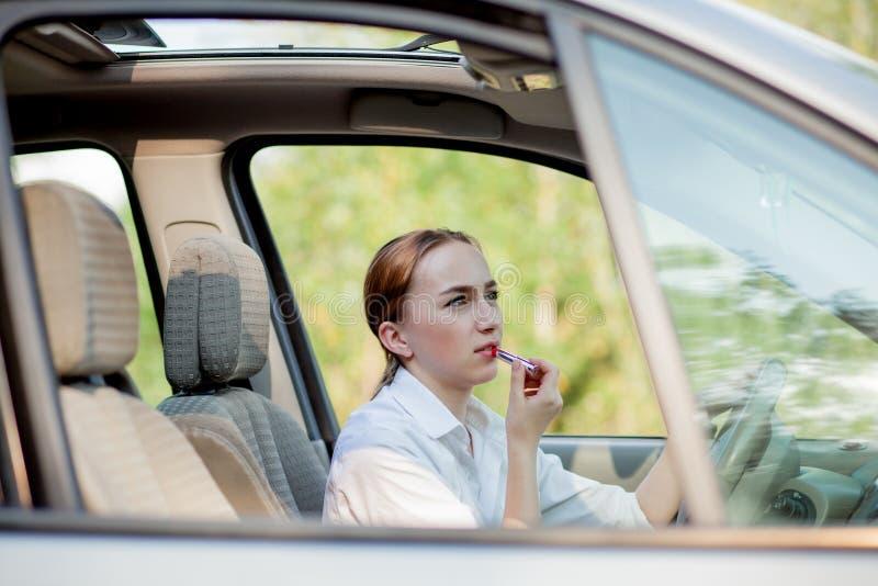 Concepto de conducci?n del peligro El adolescente pelirrojo del conductor de la mujer joven que pinta sus labios que hacen la apl imagenes de archivo