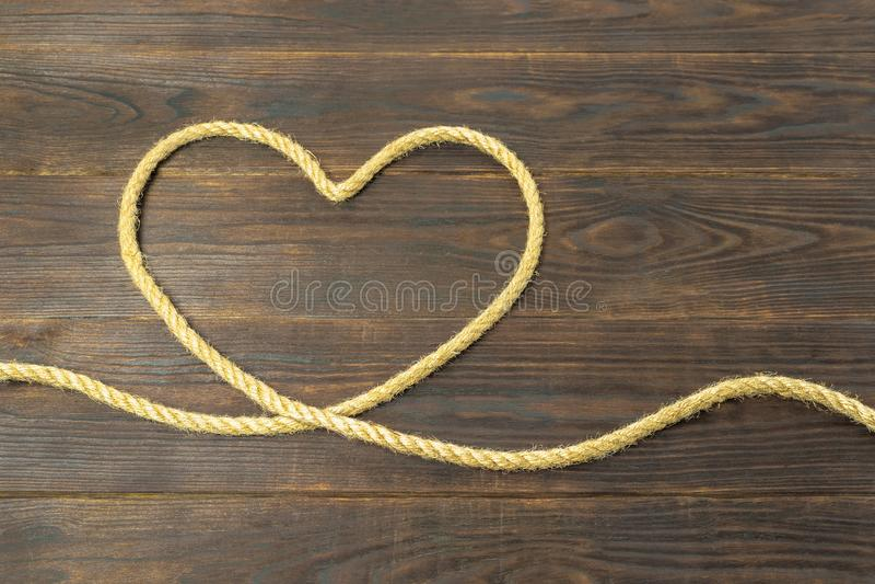 Concepto de corazón de las cuerdas del yute, amor, marco para la tarjeta de felicitación en fondo de madera marrón foto de archivo
