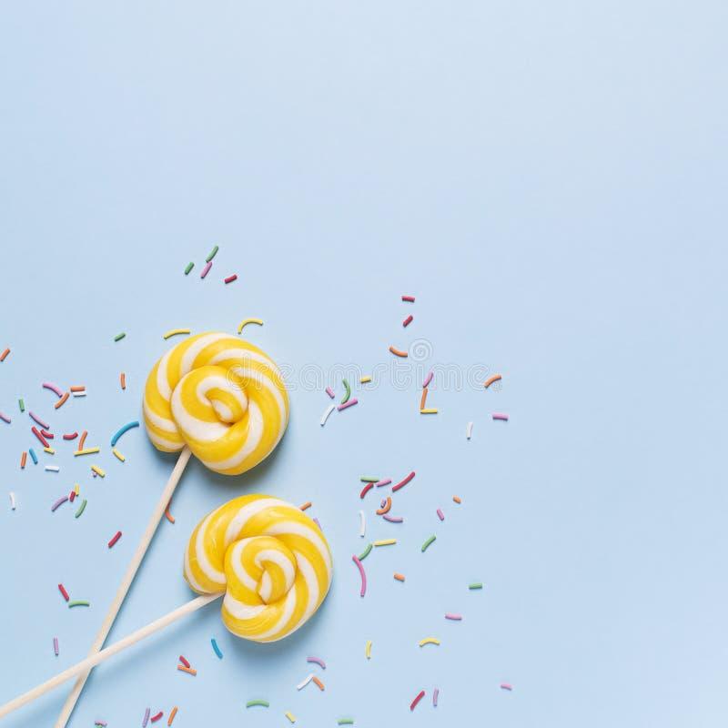 Concepto de cumpleaños y de partido con la piruleta en bakground en colores pastel azul fotos de archivo