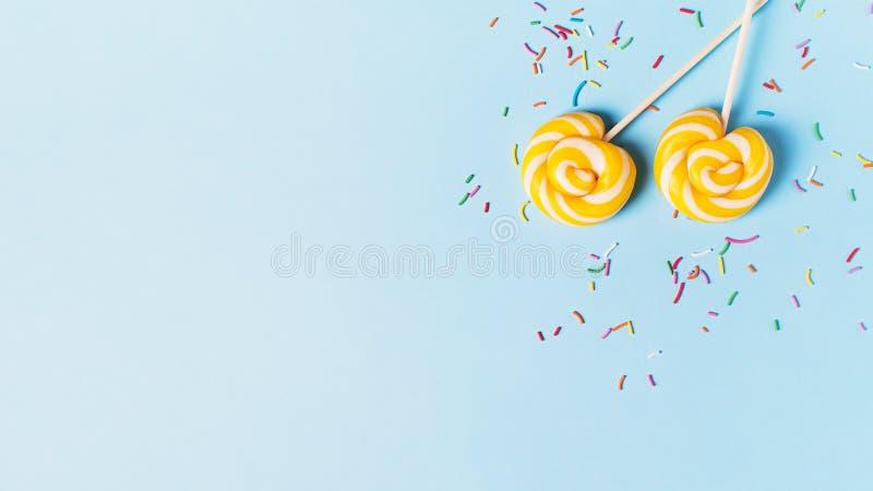 Concepto de cumpleaños y de partido con la piruleta en bakground en colores pastel azul imagen de archivo